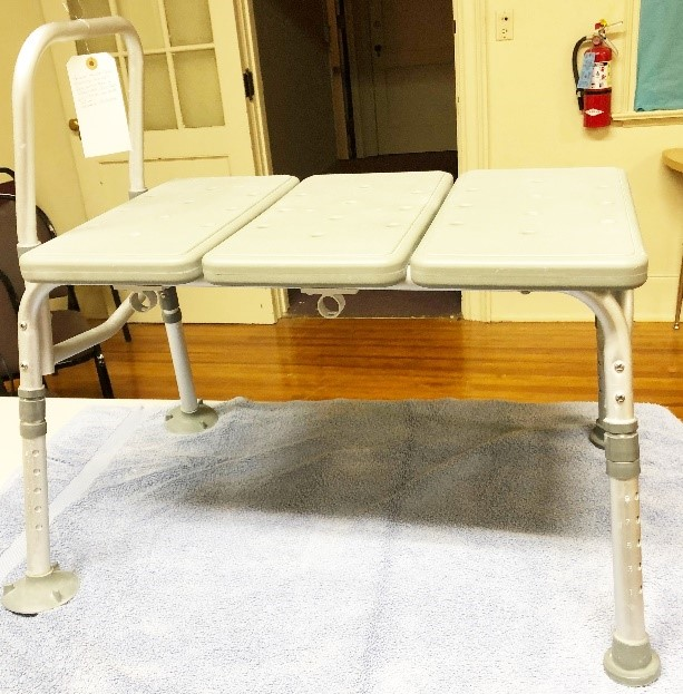 Shower bench, enable patient to slide from outside shower to inside shower, over raised threshold. Leg height adjustable.