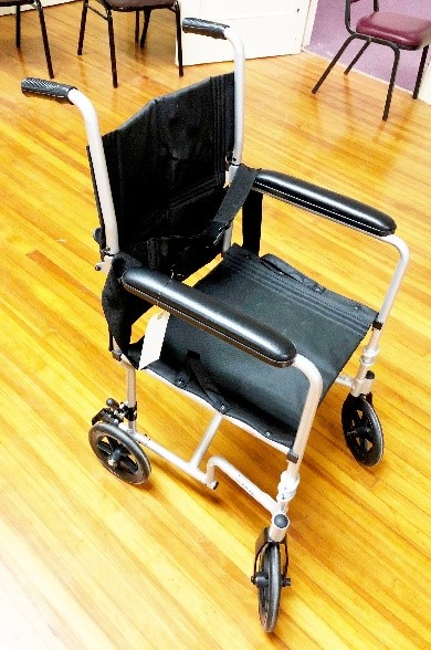 Transport only wheel chair. Notice no foot rests, large wheels, and only small ...